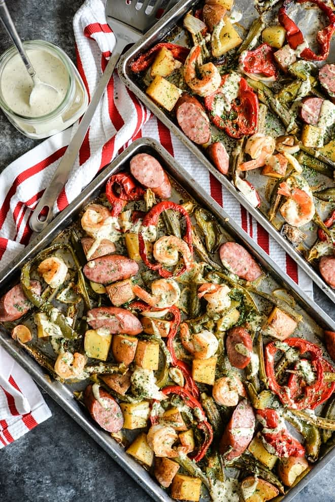 overhead view of a sheet pan loaded with sausage, shrimp, potatoes, asparagus, and red bell peppers with a creamy sauce drizzled over it on top of a dark grey table and red striped napkin