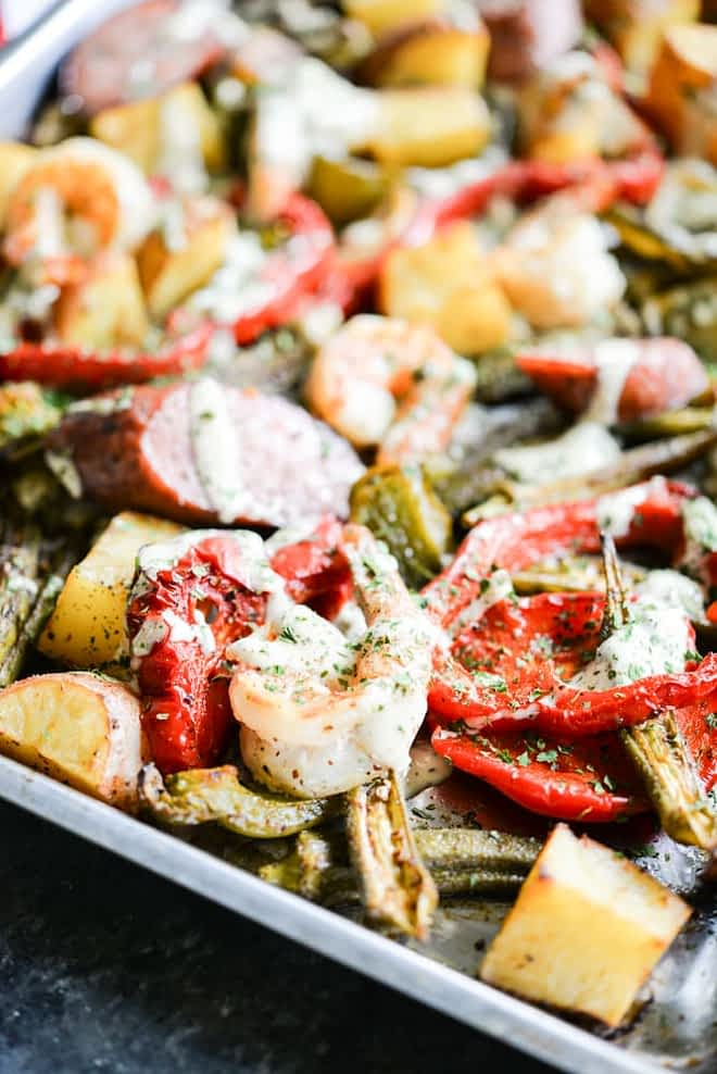 a sheet pan loaded with sausage, shrimp, potatoes, asparagus, and red bell peppers with a creamy sauce drizzled over it