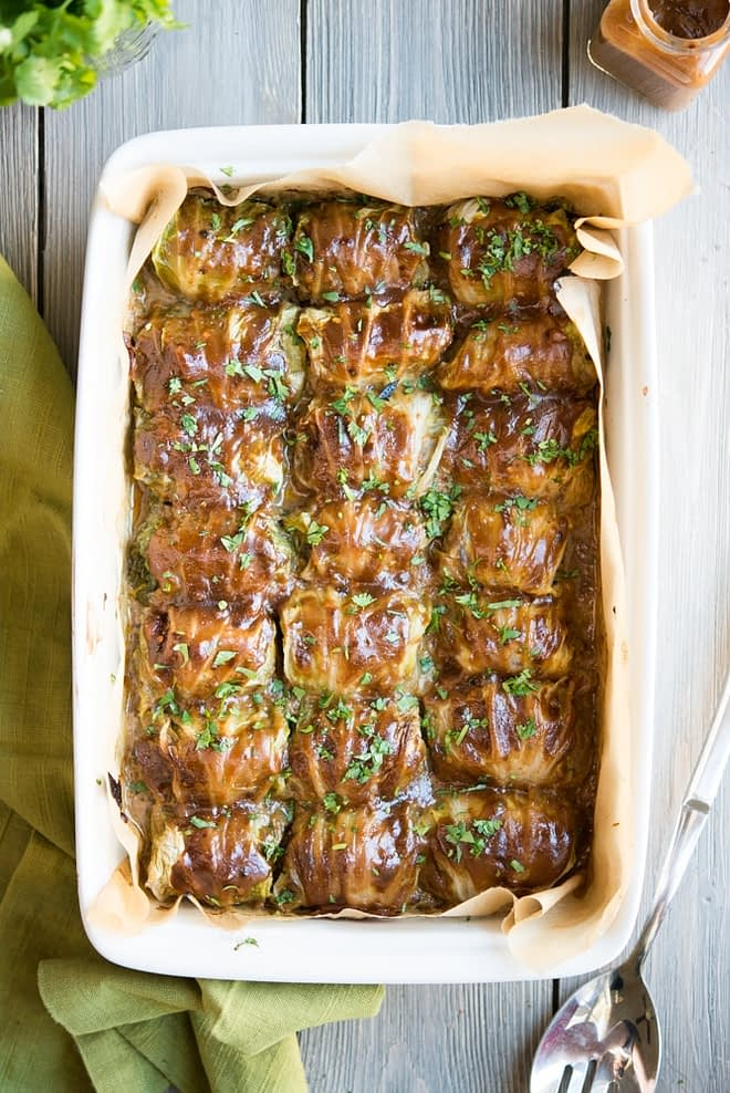 a white casserole dish filled with asian cabbage rolls and garnished with chopped cilantro