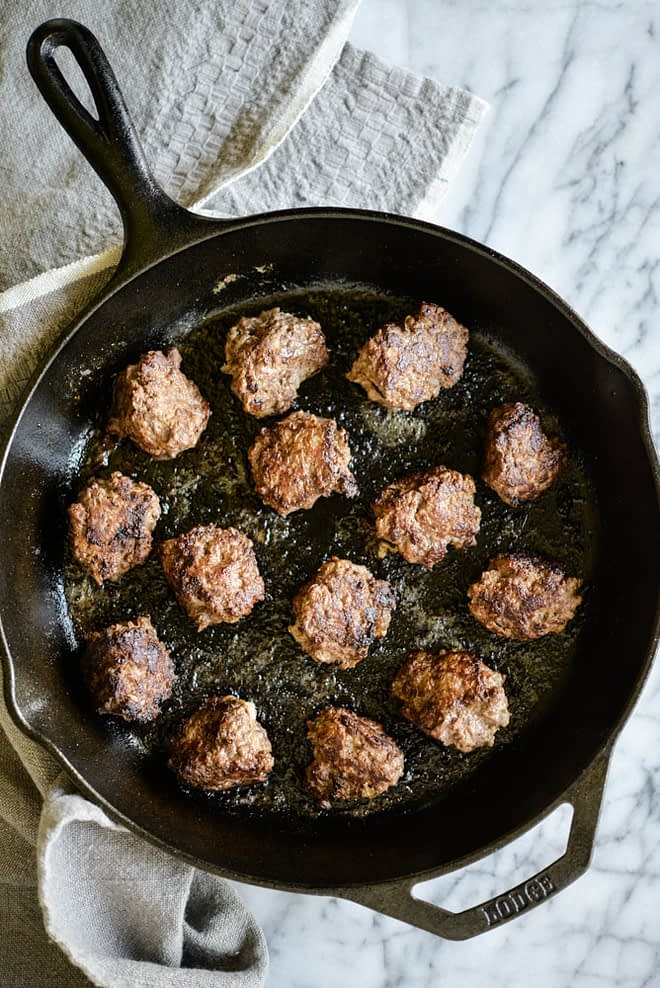 overhead of view of a cast iron skillet filled with chicken liver meatballs