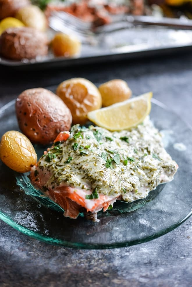 This herb crusted salmon and potato bake is an easy way to get dinner party-worthy meal on the table. A whole salmon filet is topped with a simple, but flavorful lemon-herb sauce and accompanied by crisp baby potatoes!