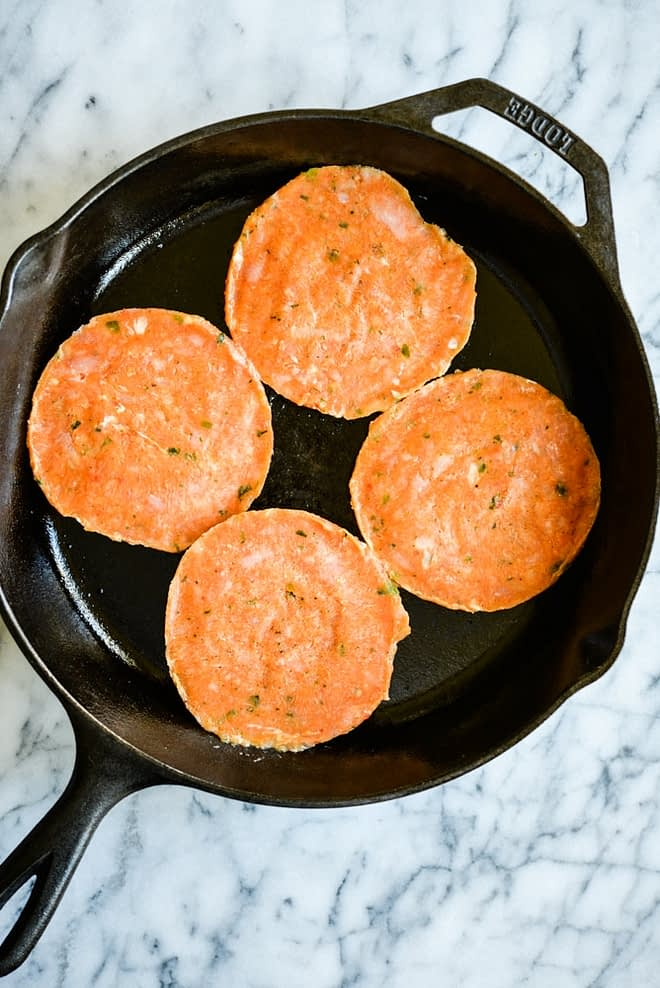 frozen tribali chipotle chicken patties in a cast iron skillet