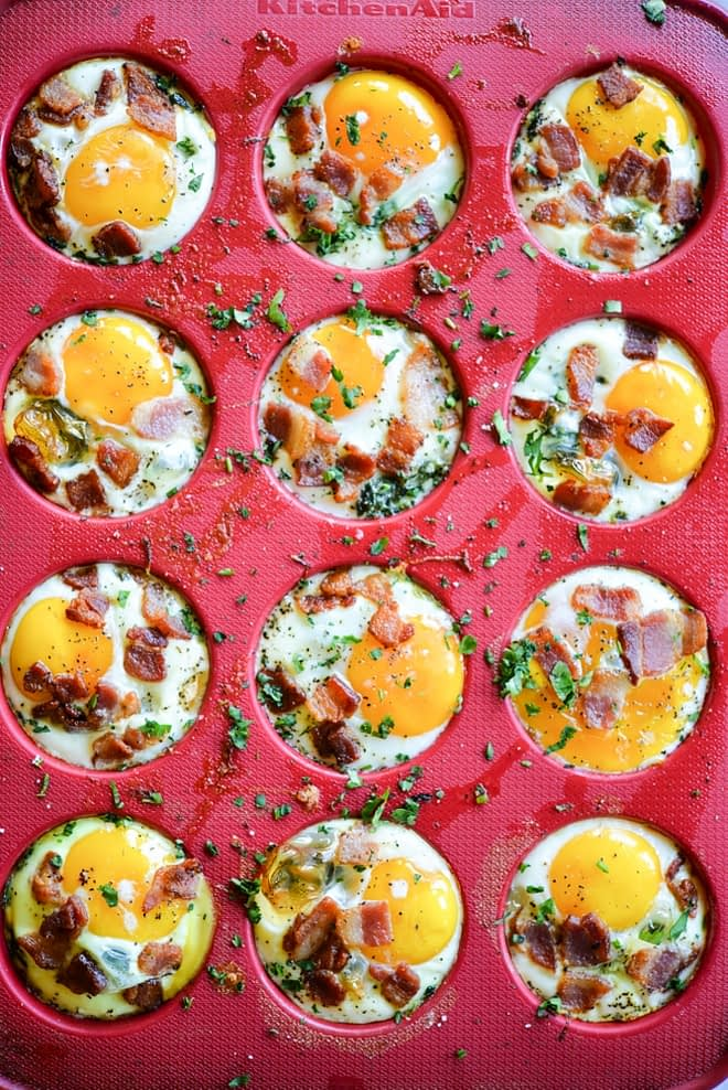 overhead view of balanced breakfast egg cups in a red silicone muffin pan