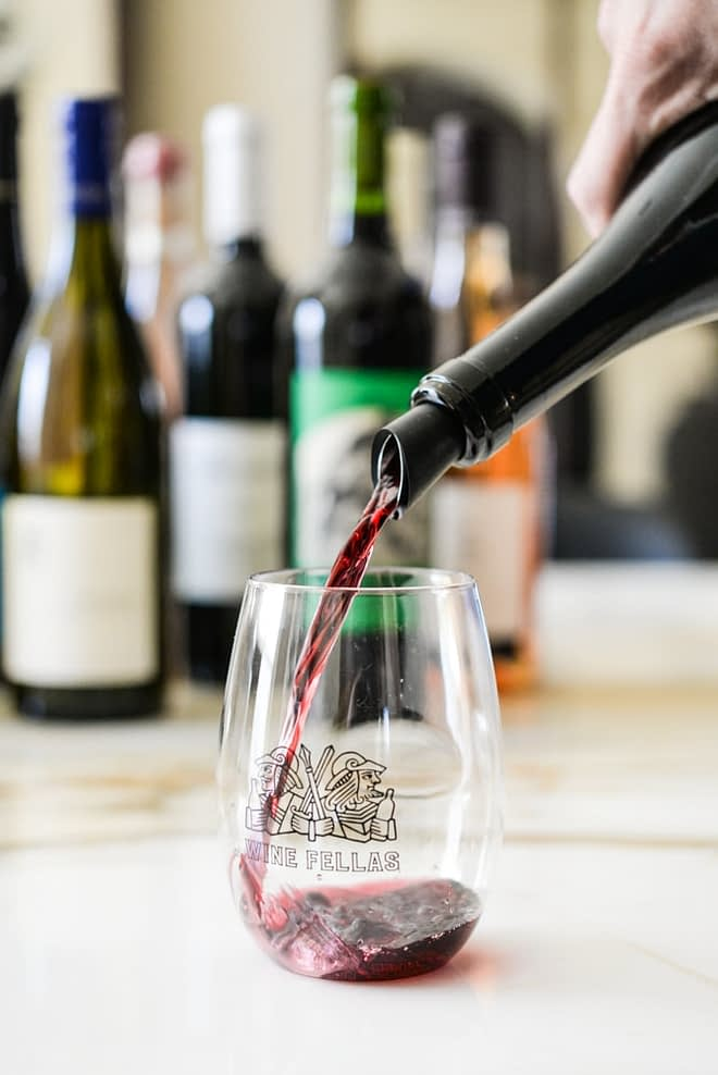 a wine bottle pouring natural red wine into a wine fellas stemless wine glass