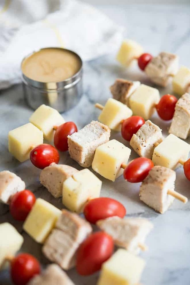 multiple chicken skewers with cheese and tomatoes and honey mustard dipping sauce