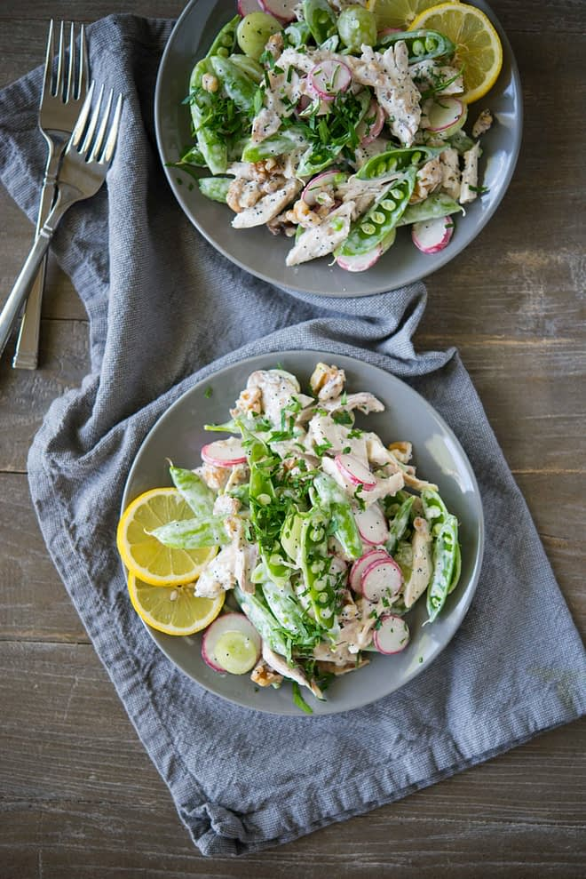 overhead view of two gray bowls full of chicken salad with snap pea radish slaw on top of a gray napkin