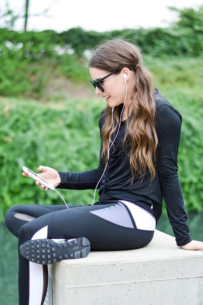 a woman with long dark pigtails sits on a concrete pillar in black activewear while wearing black sunglasses and looking down at her phone with her headphones in her ears with a green trees in the background