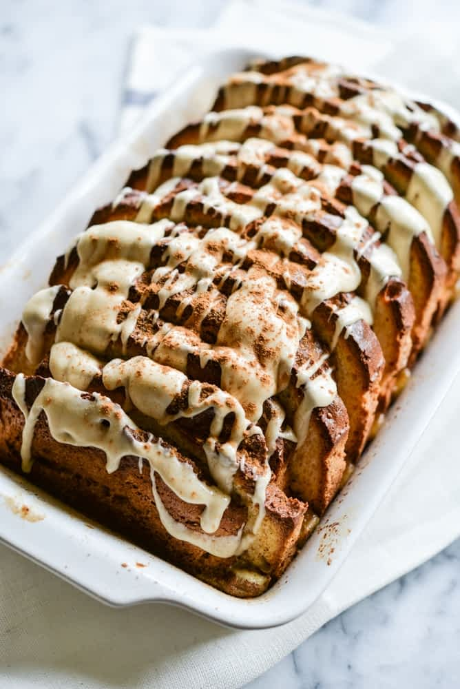 slices of gluten free cinnamon French toast bake drizzled with white frosting and sprinkled with cinnamon in a white baking pan on a white marbled tabletop
