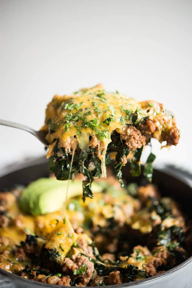 a spoon full of Beef taco casserole - you can see ground beef and shredded kale covered with melting cheese and chopped cilantro