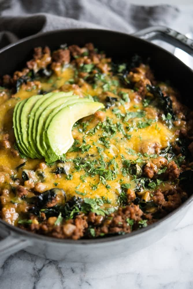 beef taco casserole in a grey cast iron dish topped with melted cheese, chopped cilantro, and sliced avocado
