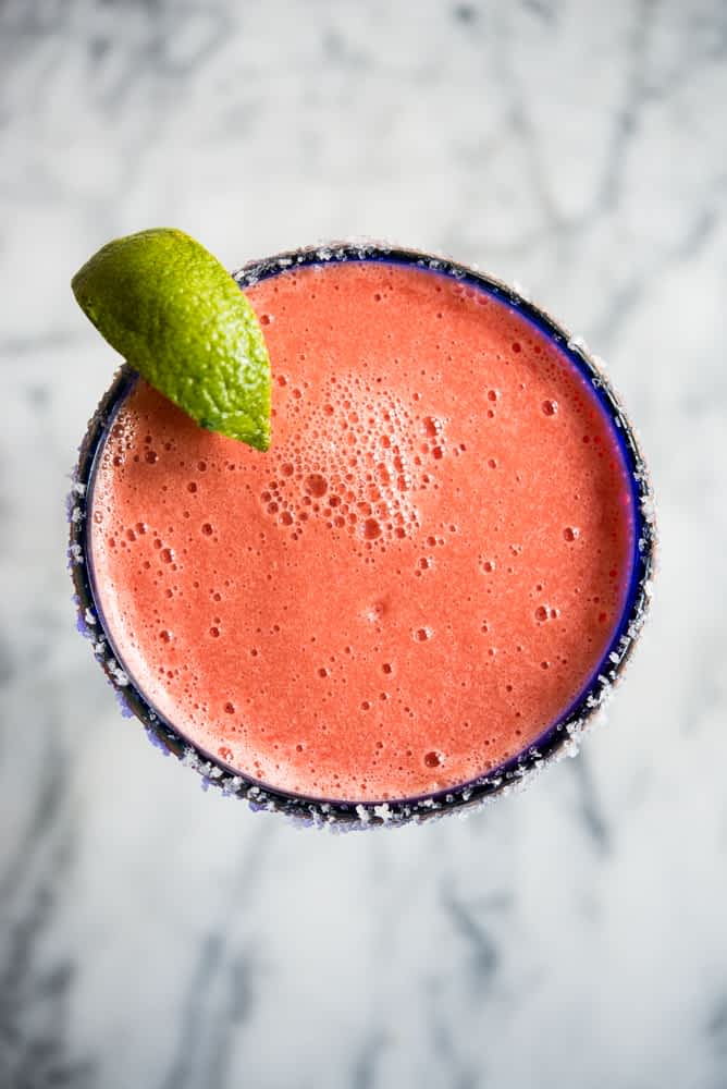 Bright pink frozen watermelon margarita in a blue-rimmed margarita glass with a lime wedge on a marble countertop.