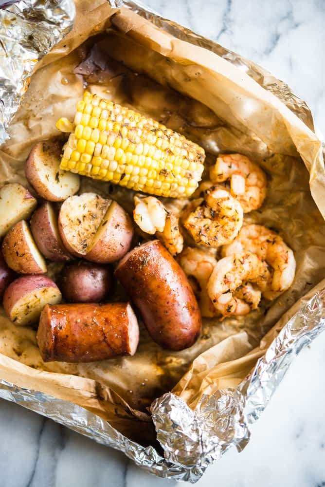 sausage, shrimp, corn, and red potatoes in a foil packet on marble for a cajun shrimp foil packet dinner