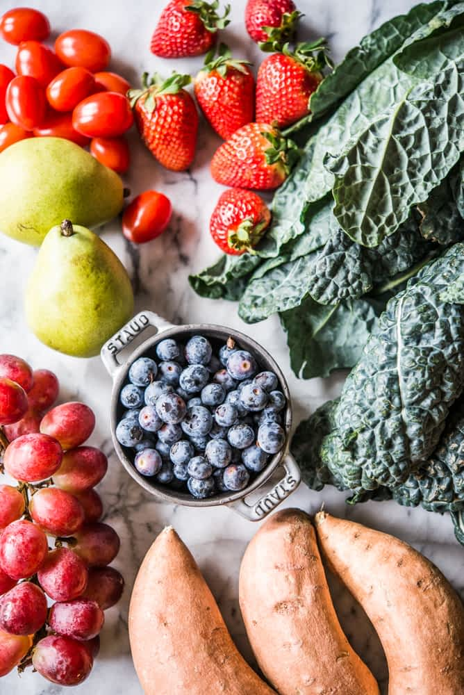 nutrient dense vegetables and fruit on a marble surface