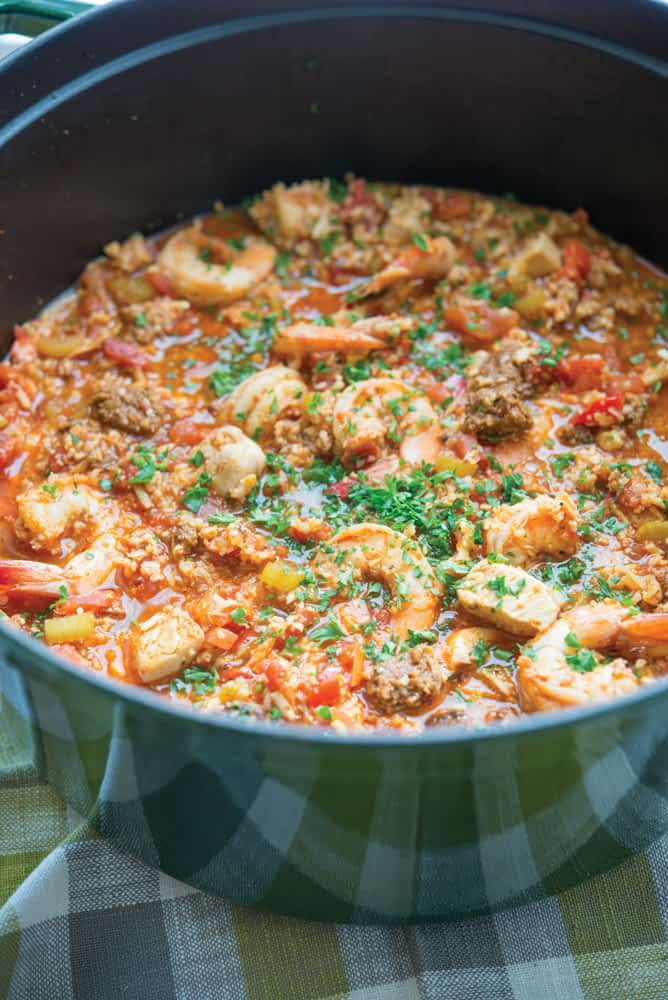shrimp jambalaya with chicken and sausauge in a large green cast iron pot with chopped parsley on top