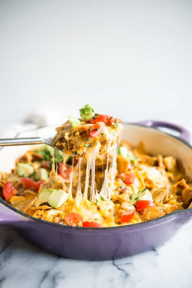a large spoon pulling a piece of chorizo migas breakfast skillet away from a casserole dish
