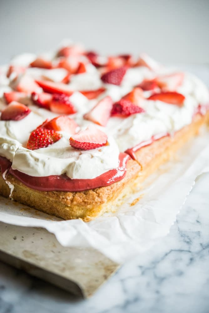 Strawberry shortcake - Vanilla sheet cake topped with whipped cream and strawberries on parchment paper on a marble slab.