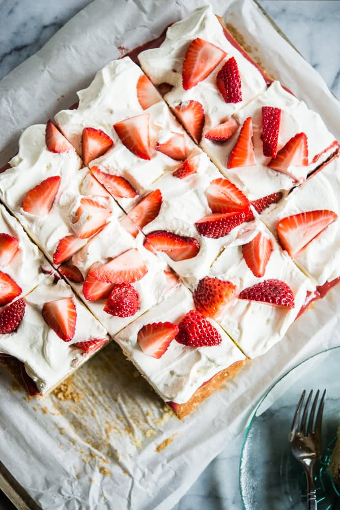 Strawberry shortcake - Vanilla sheet cake topped with whipped cream and strawberries, cut into squares with one slice missing. The cake is place on top of parchment paper on a marble slab.