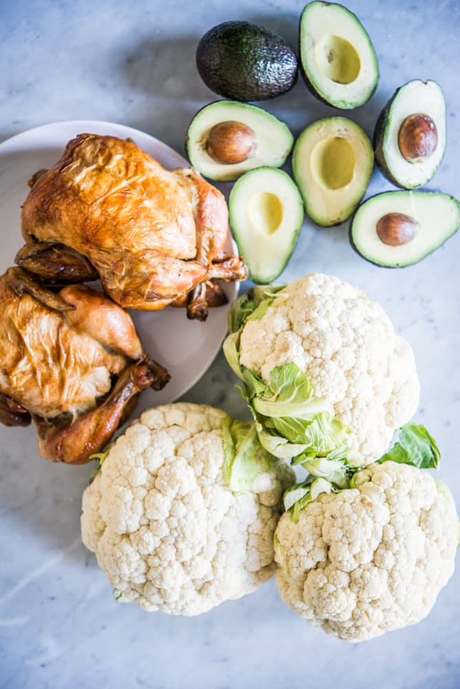 roasted chicken, avocados, and cauliflower on a marble board