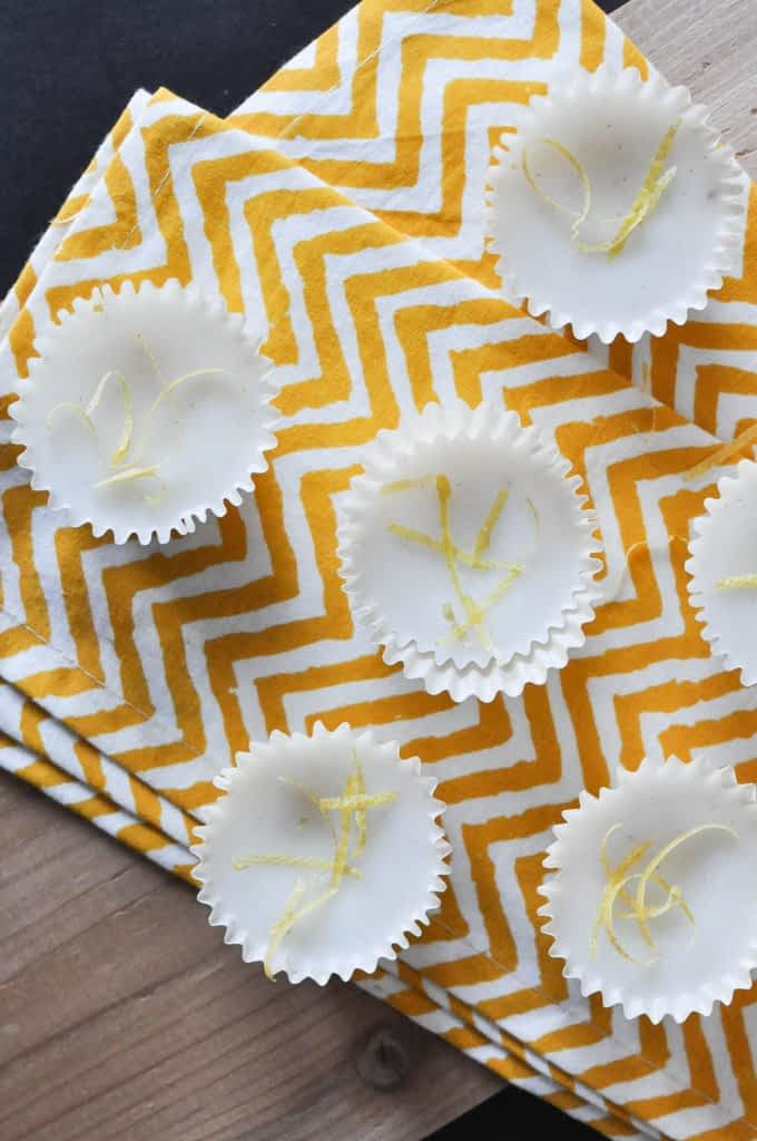 overhead view of multiple white lemon vanilla meltaways topped with lemon zest and placed on a yellow zig zag napkin