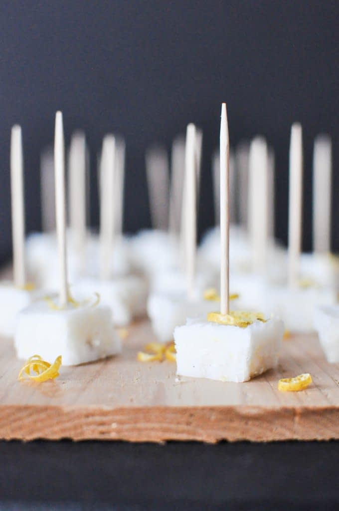 multiple squared white lemon vanilla meltaways garnished with lemon zest and stuck with toothpicks on top of a wooden board