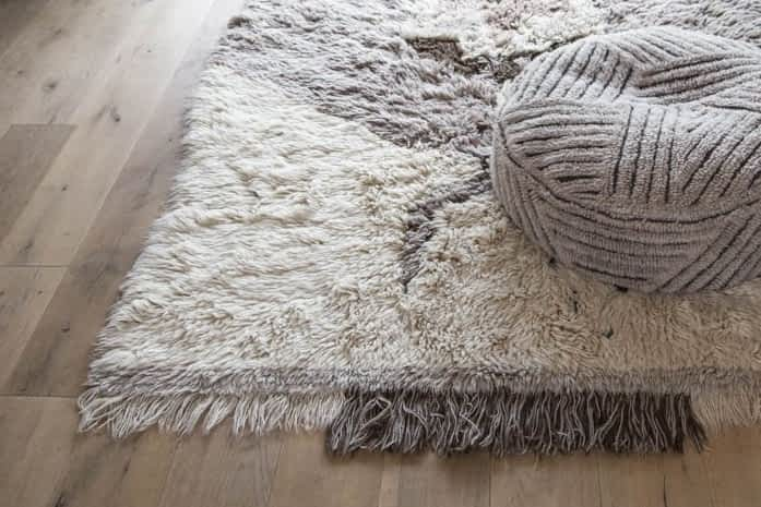non-toxic rug that is grey and white with a grey cushion sitting on top of it
