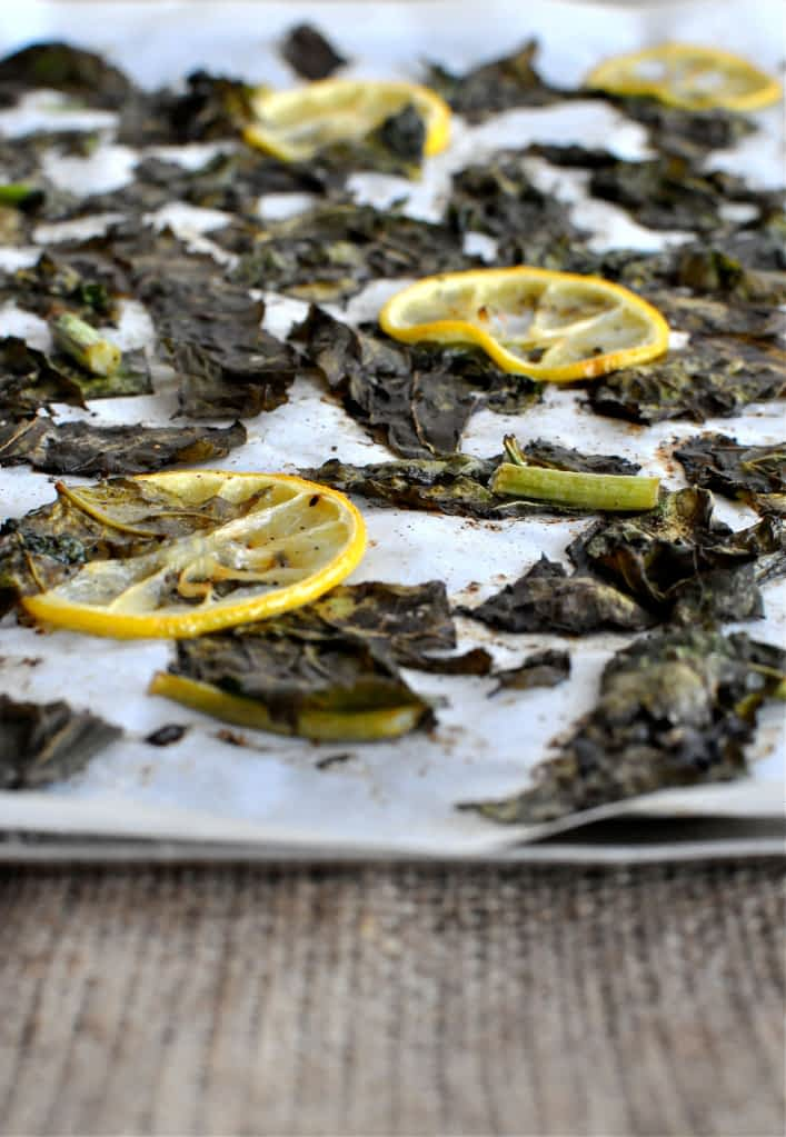 charred turnip greens and lemon slices on a sheet pan