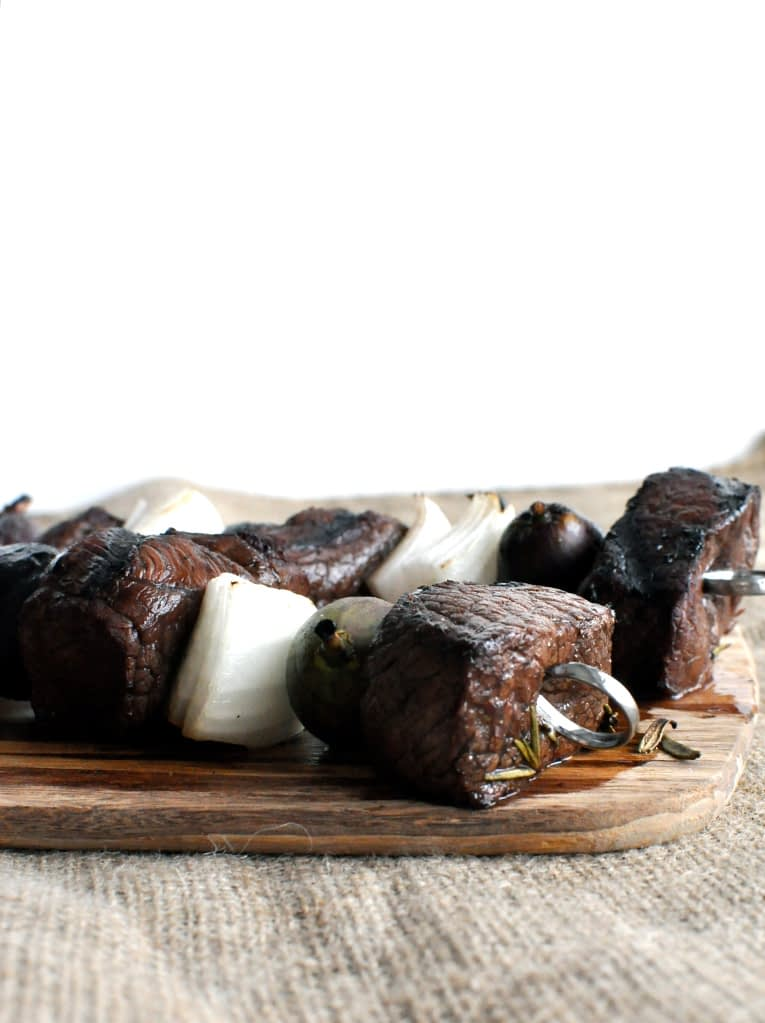balsamic fig beef kabobs on a wooden cutting board on top of a burlap tablecloth