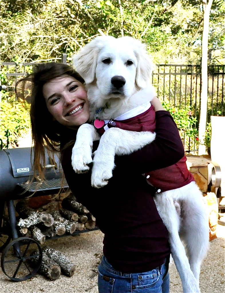 woman holding a large white dog