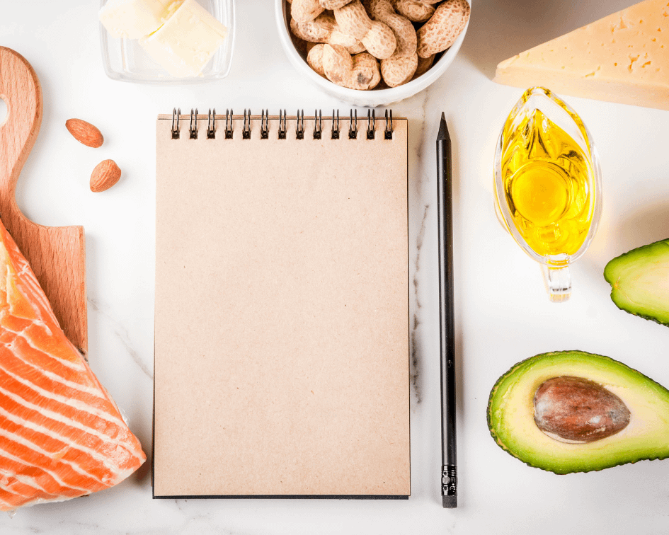 notebook, pen, avocado, oil, peanuts, and salmon on a marble board