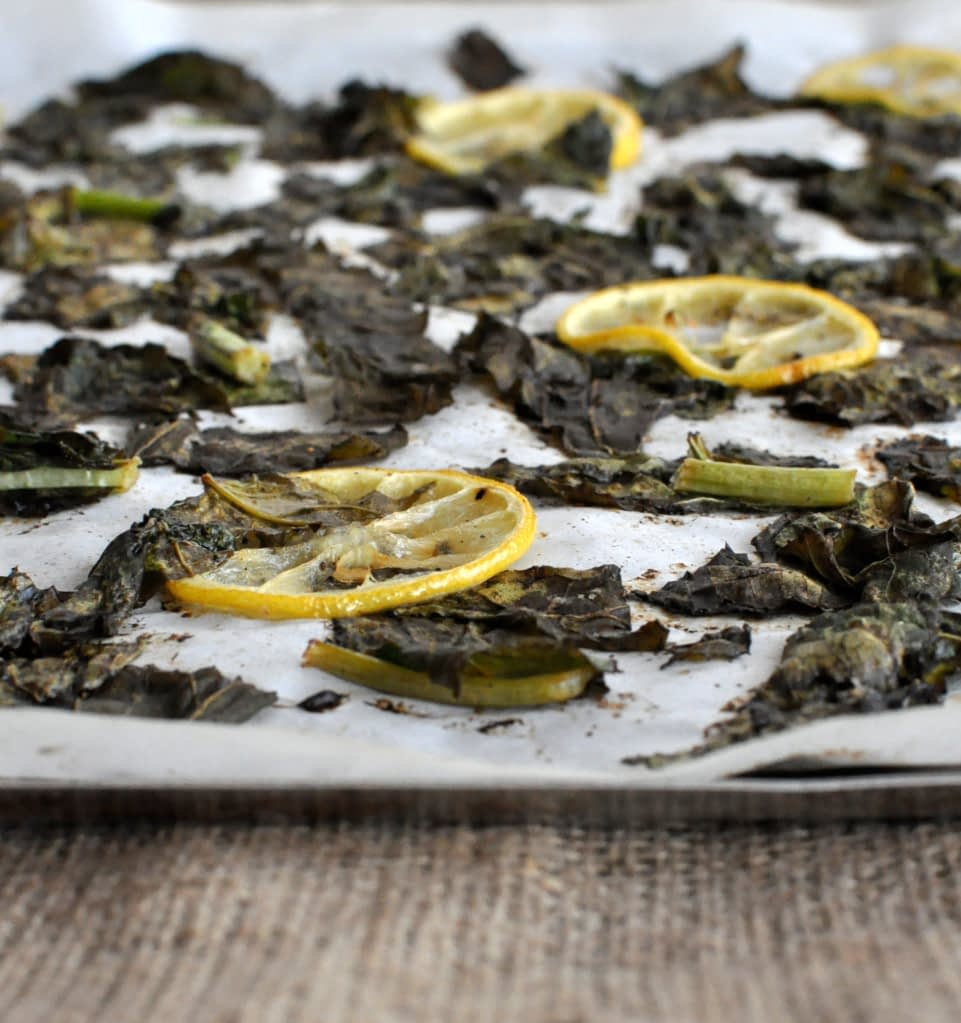 turnip greens and lemon slices on parchment paper and a sheet pan