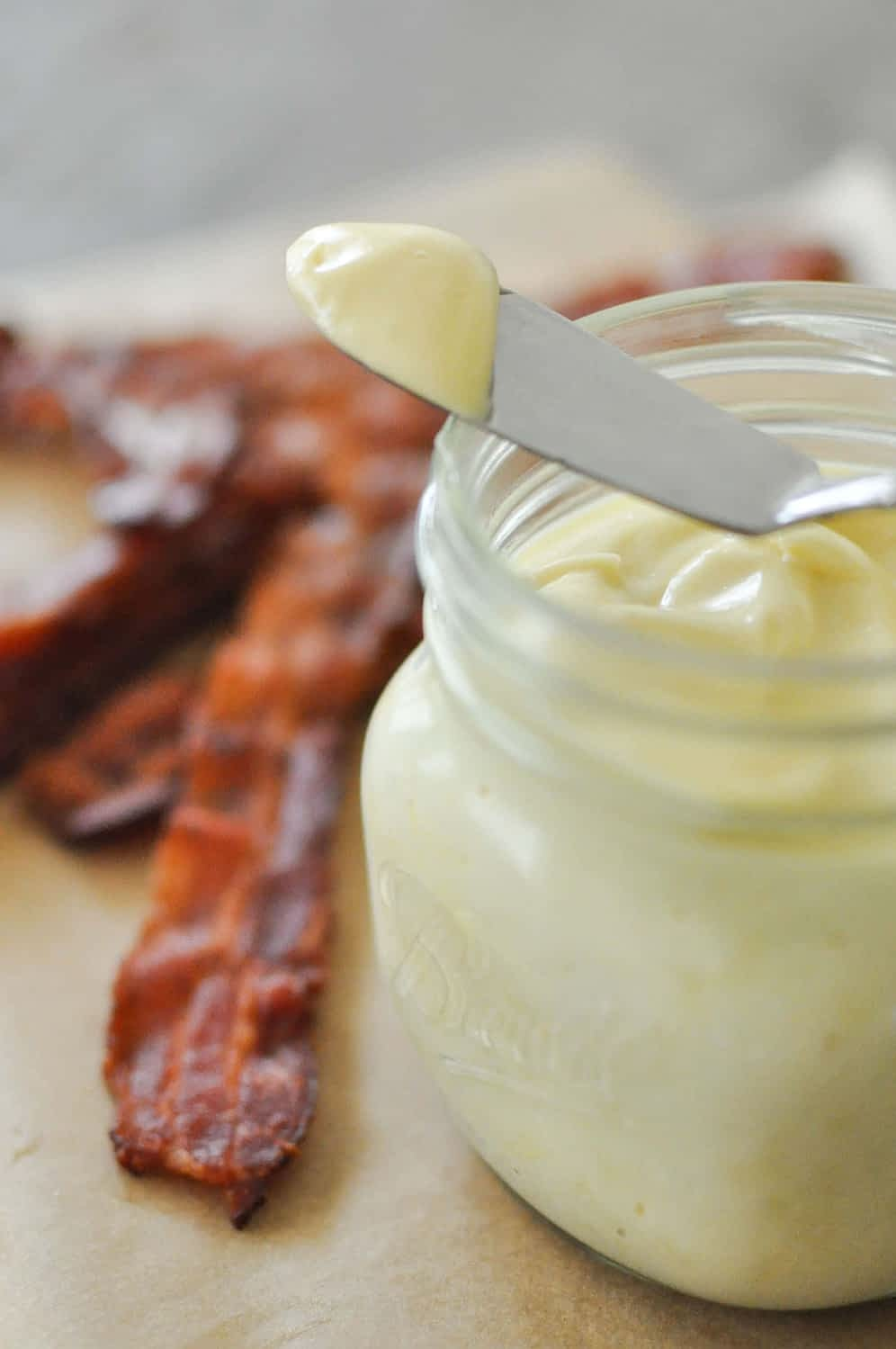 a glass jar of baconnaise on top of parchment paper next to cooked bacon with a spoon on top with a dollop of baconnaise on it