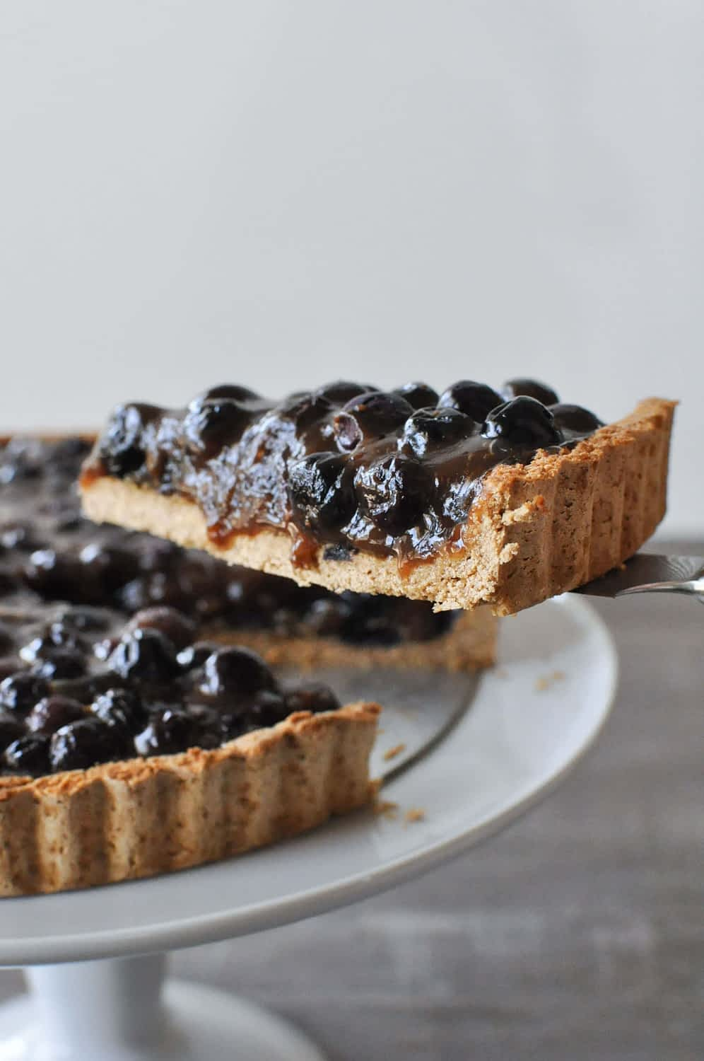 a slice of blueberry tart being lifted from a plate of blueberry tart with a pie cutter