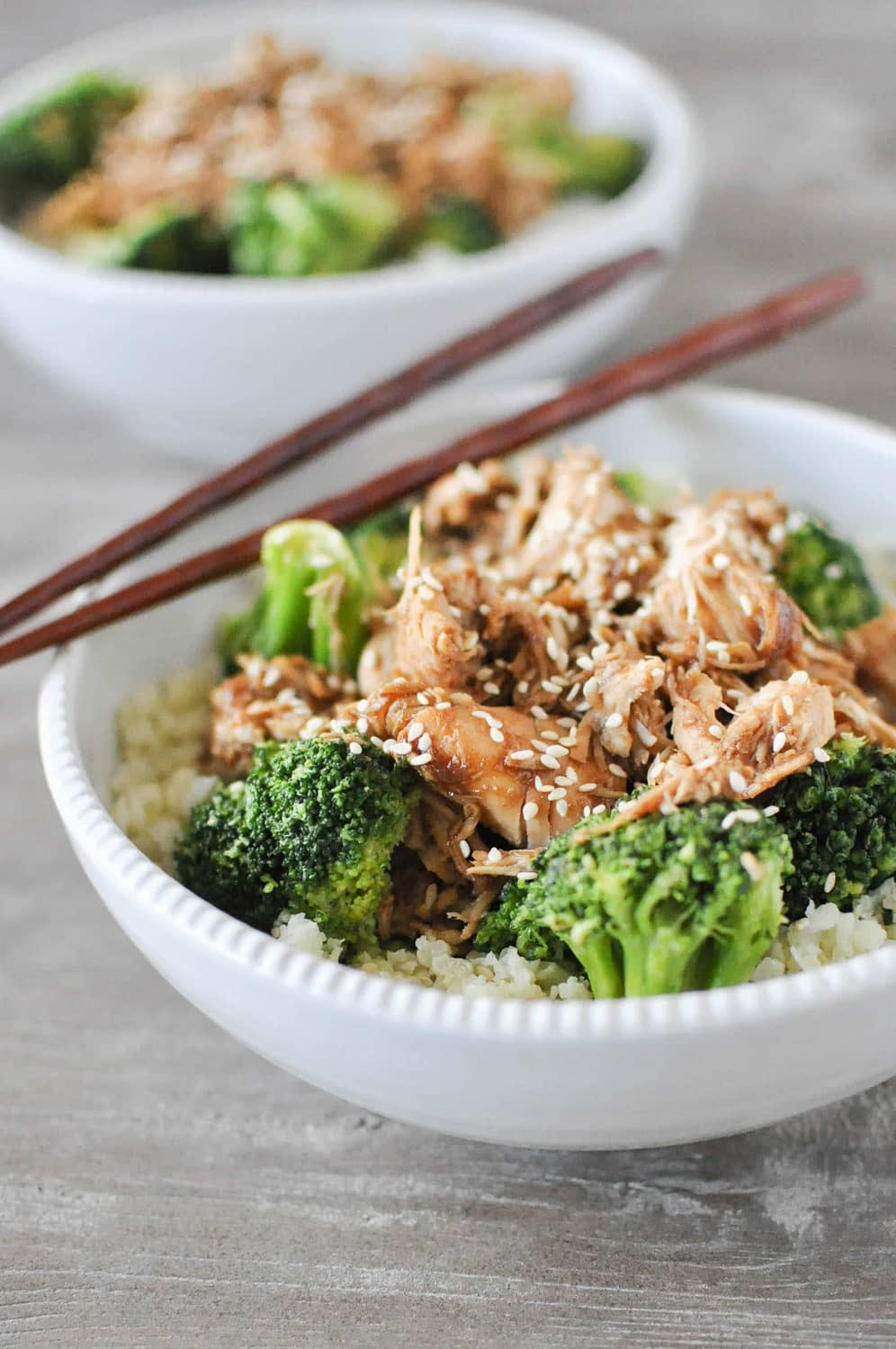 a white chicken teriyaki bowl with brown chopsticks
