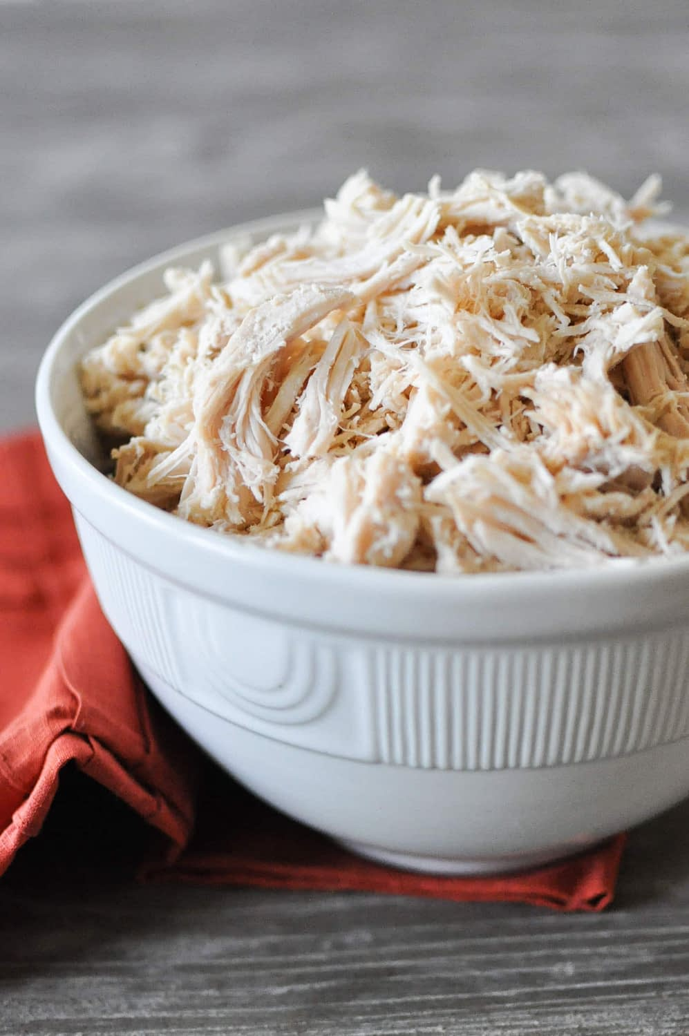 a white bowl on top of a red napkin sitting on a grey wooden table filled with cooked shredded chicken