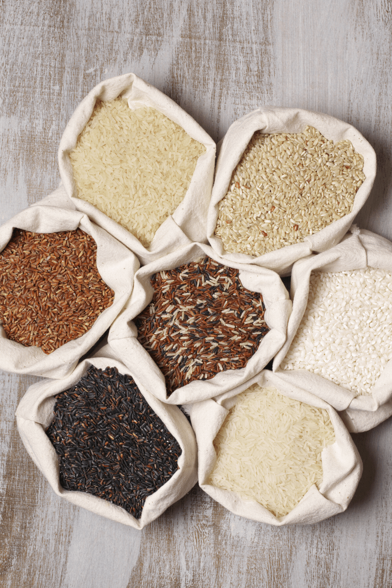 brown rice, white rice, black rice, and wild rice in burlap bags on a wooden surface