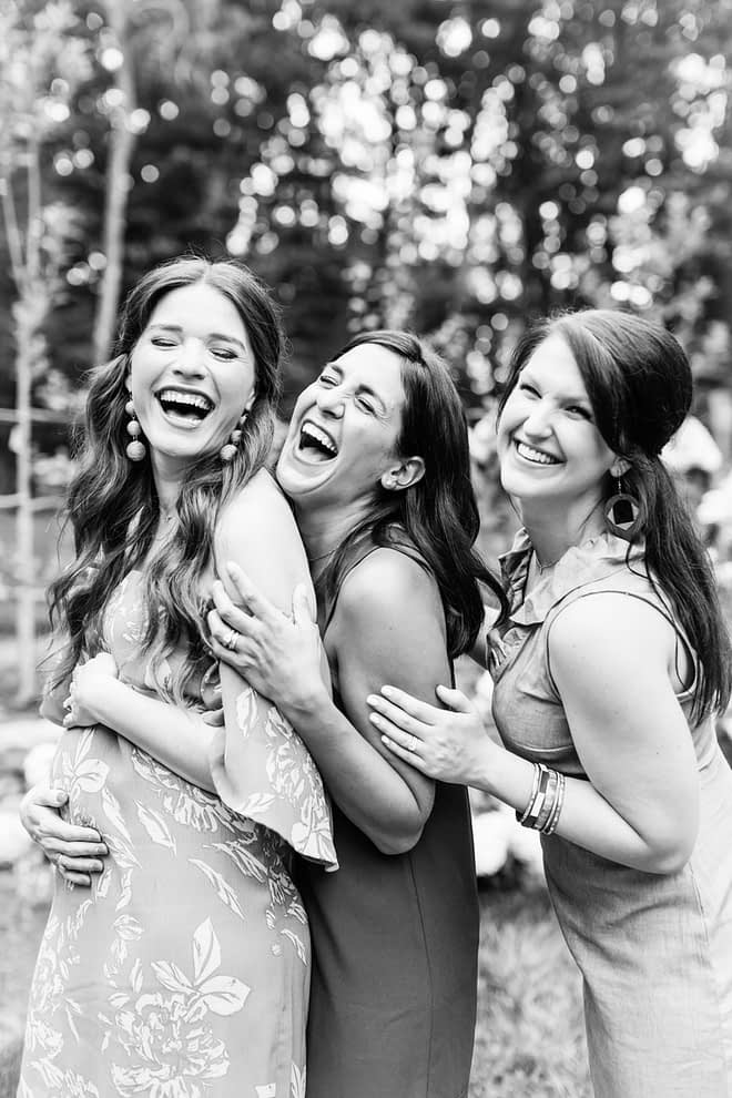 black and white image of three smiling happy women with long dark hair holding each other and one cradling her pregnant belly